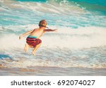 little boy play with waves on... | Shutterstock . vector #692074027