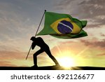 Small photo of Brazil flag being pushed into the ground by a male silhouette. 3D Rendering