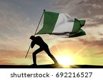 nigeria flag being pushed into... | Shutterstock . vector #692216527
