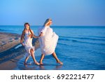 mother and daughter on the beach | Shutterstock . vector #692221477