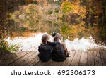 sisters sitting on a dock by a...   Shutterstock . vector #692306173
