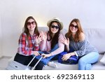 Small photo of Funny female friends together collect large gray and blue suitcases, add up all necessary things for class holiday in another country on sea. Young women fool around and laugh, measure glasses and