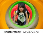 Small photo of Asian kid fun and happy from play a donus ring in playgroung in her pre school