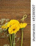Small photo of Overhead view of yellow Sarcoma Awareness ribbon by flowers on wooden table