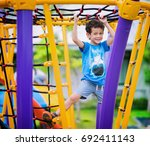 a boy climb a rope in... | Shutterstock . vector #692411143