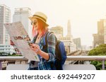 woman westerner looking at map... | Shutterstock . vector #692449207