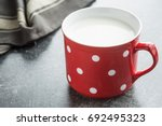 milk in red mug with white... | Shutterstock . vector #692495323