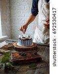 confectioner decorates a blue...   Shutterstock . vector #692530417