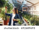 Small photo of Young lady chosing plants for her backyard in a garden supply store, shopping for flowers. Summer is the best time to care for home.