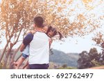 asian father carrying two child ... | Shutterstock . vector #692762497