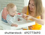 a woman is feeding a child | Shutterstock . vector #692773693