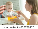 a woman is feeding a child | Shutterstock . vector #692773993