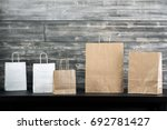 Small photo of Different blank shopping bags placed on black table. Wooden plank wall background. Purchase, advert concept. Mock up