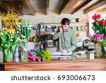Small photo of Male attractive florist accepting orders over a phone and taking notes in a notebook in a flower shop. Man assistant or owner in floral design studio, making decorations. Flowers delivery service.