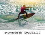 silhouette surfing at sunset.... | Shutterstock . vector #693062113