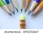 Small photo of group of pencils standing in a semicircle humiliating small eraser. concept of a schoolchild in new school or bad pupils bully good pupil