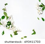 Stock photo creative layout of flowers composition frame made of white flowers and green leaves flat lay top 693411703