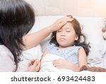 mother measuring temperature of ... | Shutterstock . vector #693424483