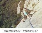 rock climber ascending a... | Shutterstock . vector #693584347