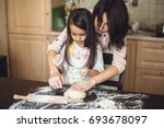 mother and daughter cooking at... | Shutterstock . vector #693678097
