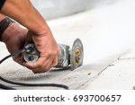 Small photo of Worker grind hard floor. Worker with high shear grinder cut and mill cement or asphalt or concrete to separate surface of floor away. Danger job.