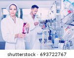 Small photo of Two young efficient researchers in white coat checking wine acidity and sugar saturation in chemical laboratory
