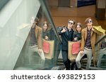 three girlfriends on escalator... | Shutterstock . vector #693829153