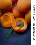 Small photo of Apricot and halve with stone on dark background