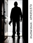 Small photo of Intruder standing at doorway threshold, in silhouette with handgun