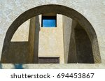 Small photo of A view of courtyard through an arch, a strong visual element in architecture. Strong sunlight and shadows suggest a desert locale.