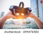 vr goggles in male hands. man... | Shutterstock . vector #694476583