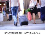 man walking with suitcase ... | Shutterstock . vector #694523713