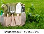 garden tools in a garden | Shutterstock . vector #694583143