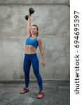 girl raises a dumbbell in a... | Shutterstock . vector #694695397
