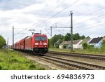 """Small photo of Lauchhammer, Brandenburg, Germany - 20 May 2017: A freight train (""""Güterzug"""") of the Deutsche Bahn (""""DB Regio Südost"""") passses Lauchhammer. The Bombardier locomotive 185 391-0 is owned by DB Cargo AG."""