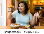 asian woman weighs frenchfries... | Shutterstock . vector #695027113