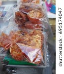 """Small photo of Sweet preserved Thai fruit """"Bael"""" (Aegle marmelos) in transparent plastic bag from street food stall"""