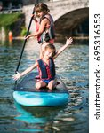 Small photo of Two Little girls on sup board paddling on lake
