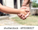 young hands holded by old ones... | Shutterstock . vector #695338327