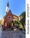 Small photo of TALLINN, ESTONIA - JULY 26, 2017: Red building facade and tall tower of church of Holy Spirit in the old town of Tallinn, Estonia on July 26, 2017