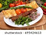 adana kebab is a long  hand... | Shutterstock . vector #695424613