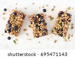 Small photo of Superfood breakfast bars with oats and blueberries, above view on white marble background