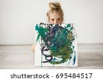 Small photo of Studio shot of beautiful little blonde girl holding and hiding by the big picture, looking at the camera with cunny and joyful expression. Cute child with hair bun, freckles and blue eyes showing