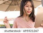 asian girl watching tablet | Shutterstock . vector #695521267