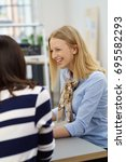 Small photo of Happy young businesswoman laughing during a meeting with a female colleague in an over the shoulder natural view