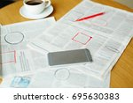 Stock photo newspaper with highlighted vacancy adverts smartphone cup of coffee and pen on table 695630383