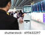 Small photo of Businessman suit passenger use self driving chcek-in robots assistant for ticket and accompany them to their gate at international airport.