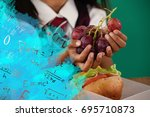Small photo of Digital composite image of algebraic formulas against schoolgirl having grape fruit