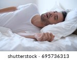 Small photo of Man snoring because of sleep apnea lying in the bed