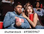 young scared couple watching a... | Shutterstock . vector #695805967